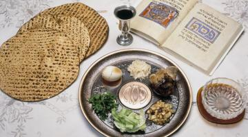 Passover table with matzah, hagaddah, seder plate